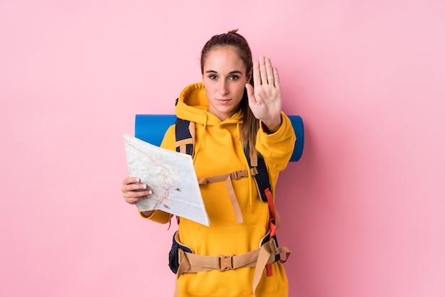 Кавказская женщина молодого путешественника изолировала положение с протянутой рукой, показывая знак остановки, предотвращая вас.