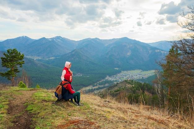 山で休んでいる若い旅行者のカップルの男性と女性がバックパックでハイキング