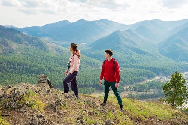 若い旅行者のカップルは、バックパックでハイキングする山の男性と女性の頂上に立っています