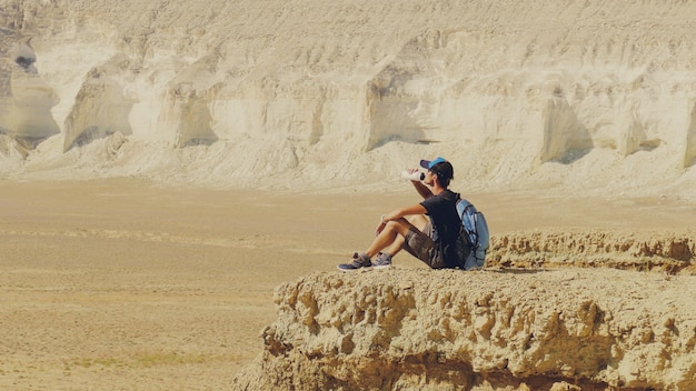 A young traveler drinks water against the rocks