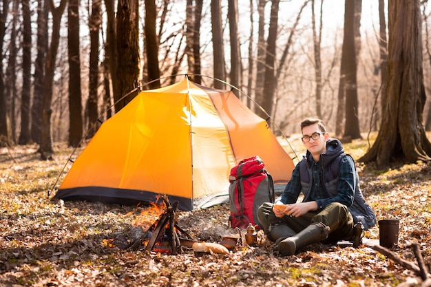 A young traveler in the forest is resting near the tent and cooked breakfast in nature