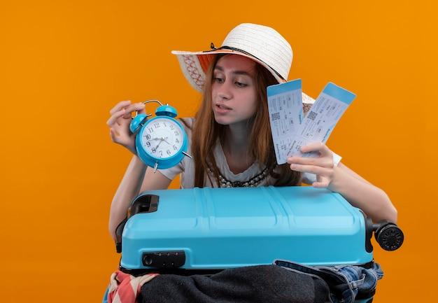 Ragazza giovane viaggiatore che tiene i biglietti aerei e sveglia con la valigia e guardando la sveglia sulla parete arancione isolata