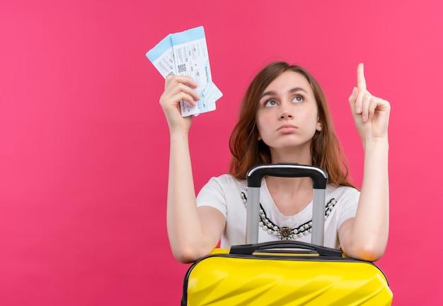 孤立したオレンジ色の壁にスーツケースと飛行機のチケットと目覚まし時計を保持している若い旅行者の女の子