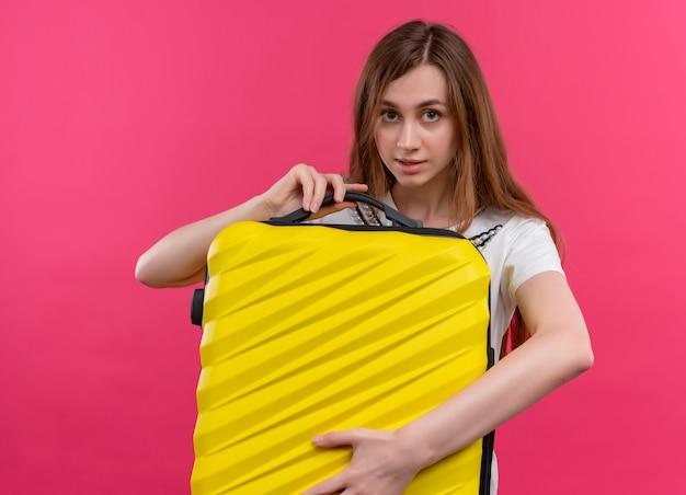 Молодая девушка путешественника держит чемодан и смотрит на изолированную розовую стену