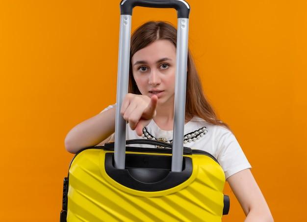Молодая девушка путешественника держит чемодан и указывает и смотрит на изолированную оранжевую стену