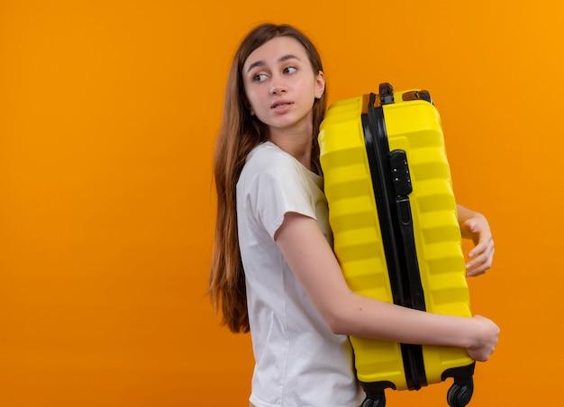 Молодая путешественница девушка держит чемодан, глядя на левую сторону на изолированной оранжевой стене с копией пространства
