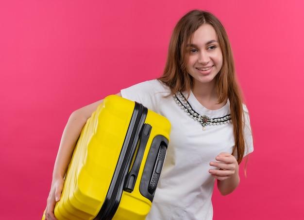 Молодая путешественница девушка держит чемодан на изолированной розовой стене