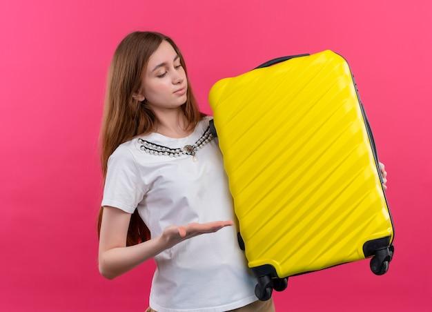 Ragazza del giovane viaggiatore che tiene la valigia e che indica con la mano sulla parete rosa isolata