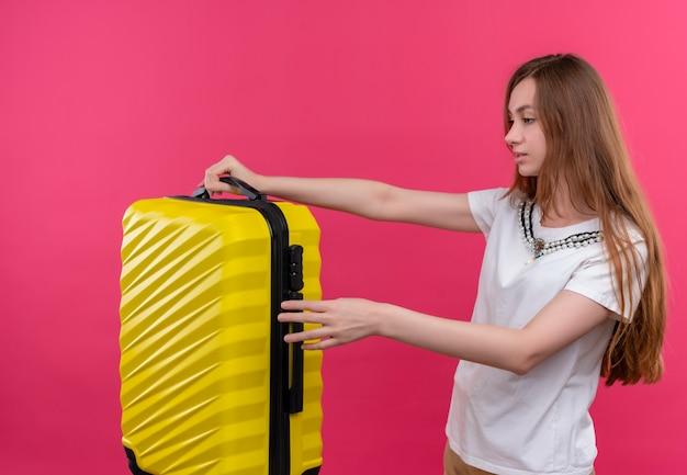 Молодая путешественница девушка держит чемодан, стоя в профиль на изолированной розовой стене