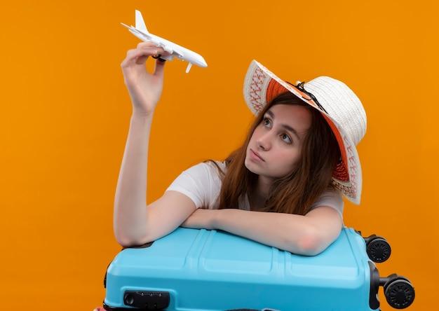 Ragazza giovane viaggiatore che indossa il cappello che tiene aereo modello e guardandolo e mettendo il braccio sulla valigia sulla parete arancione isolata