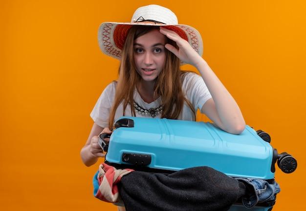 布でいっぱいのスーツケースを持って帽子をかぶって、コピースペースで孤立したオレンジ色の壁を見て頭に手を置く若い旅行者の女の子
