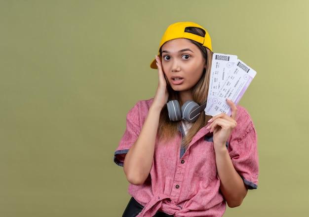 首にヘッドフォンを付けた帽子をかぶったピンクのシャツを着た若い旅行者の女の子が、顔に手を当てて驚いて驚いたように見える航空券を持っています