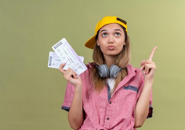 Молодая девушка-путешественница в розовой рубашке в кепке с наушниками на шее, держащая авиабилеты, смотрит вверх озадаченно, указывая пальцем вверх