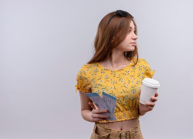 飛行機のチケットとプラスチック製のコーヒーカップを保持し、孤立した白い壁に縦断ビューで立っているチケットを見て頭にサングラスをかけている若い旅行者の女の子