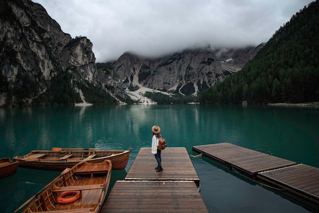Young traveler girl with hat and vintage backpack on jetty of lago di braies surrounded by the mountains of the italian alps
