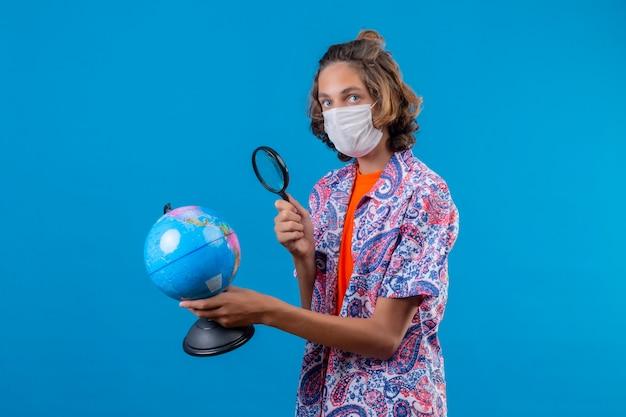 旅行スーツケースを持って、青い背景の上に立って興味を持って世界中で虫眼鏡を通して見る顔の保護マスクを身に着けている若い旅行者男