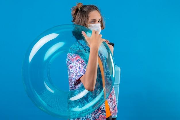 Ragazzo giovane viaggiatore che indossa la maschera protettiva per il viso tenendo la valigia da viaggio e anello gonfiabile cercando fiducioso in piedi su sfondo blu