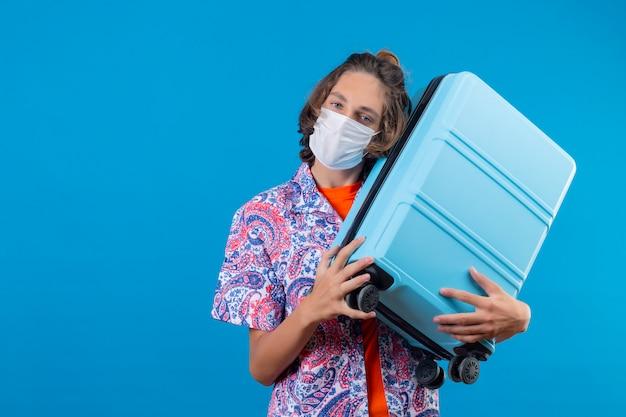 陽気で幸せな立っている探している旅行スーツケースを持って顔の防護マスクを着ている若い旅行者の男
