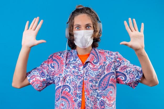 青い背景の上に立って驚いて見て降伏で手を上げるヘッドフォンで顔の防護マスクを着ている若い旅行者男