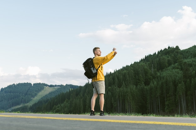 Young traveler guy in a yellow sweatshirt with backpack taking pictures of the woods