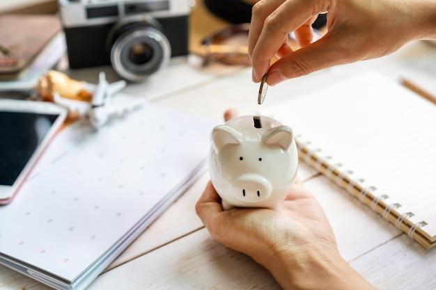 돼지 저금통을 들고 돈을 모으고 휴가 여행을 계획하는 젊은 여행자