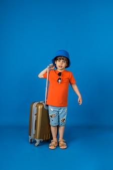 Молодой путешественник в панаме стоит с чемоданом на синей поверхности с местом для текста
