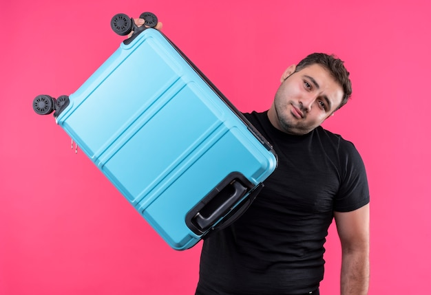 Young traveler man in black t-shirt holding suitcase confused standing over pink wall