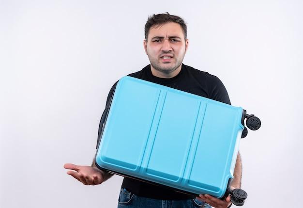 Uomo giovane viaggiatore in maglietta nera che tiene la valigia confusa e molto ansiosa in piedi sopra il muro bianco