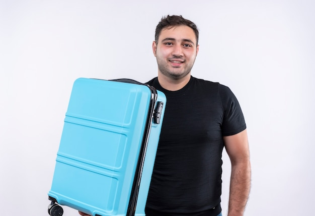 Uomo giovane viaggiatore in maglietta nera che tiene la valigia felice e positiva con il sorriso sul viso in piedi sopra il muro bianco