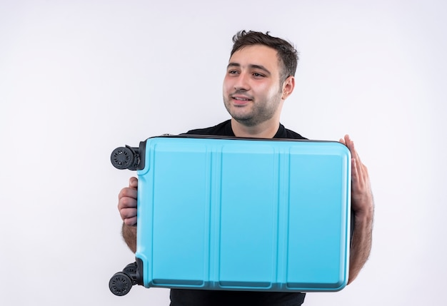 Young traveler man in black t-shirt holding suitcase looking aside smiling with happy face standing over white wall