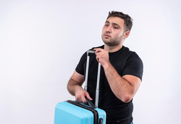 Uomo giovane viaggiatore in maglietta nera che tiene la valigia che osserva da parte con l'espressione triste sul viso in piedi sopra il muro bianco
