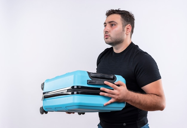 Young traveler man in black t-shirt holding suitcase looking aside with serious expression standing over white wall