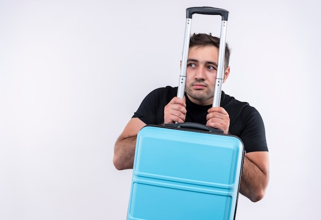 Uomo giovane viaggiatore in maglietta nera che tiene la valigia guardando da parte preoccupato con l'espressione di paura in piedi sopra il muro bianco