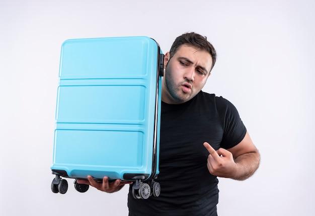 Uomo giovane viaggiatore in maglietta nera che tiene la valigia che punta con il dito indice ad esso guardando da parte in piedi ansioso sopra il muro bianco
