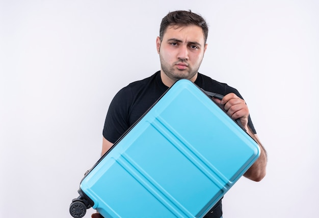 Young traveler man in black t-shirt holding suitcase with serious frowning face standing over white wall