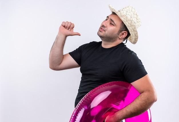 Uomo giovane viaggiatore in maglietta nera e cappello estivo che tiene anello gonfiabile che punta a se stesso soddisfatto di sé e orgoglioso in piedi sopra il muro bianco