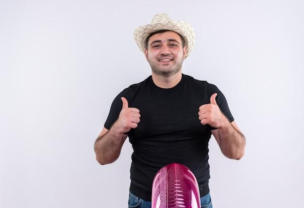 Uomo giovane viaggiatore in maglietta nera e cappello estivo che tiene anello gonfiabile che mostra i pollici in su sorridendo allegramente in piedi sopra il muro bianco
