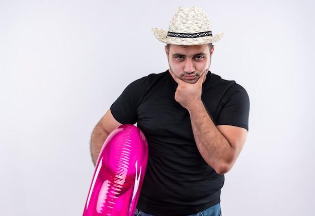 Uomo giovane viaggiatore in maglietta nera e cappello estivo che tiene anello gonfiabile con la faccia accigliata perplessa in piedi sopra il muro bianco