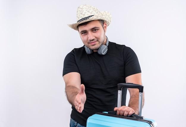 Uomo del giovane viaggiatore in maglietta nera e cappello estivo con la valigia che sembra saluto fiducioso che offre la mano che sta sopra il muro bianco