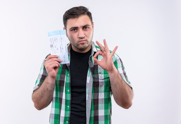 Young traveler man in checked shirt holding air tickets looking confident doing ok sign standing over white wall