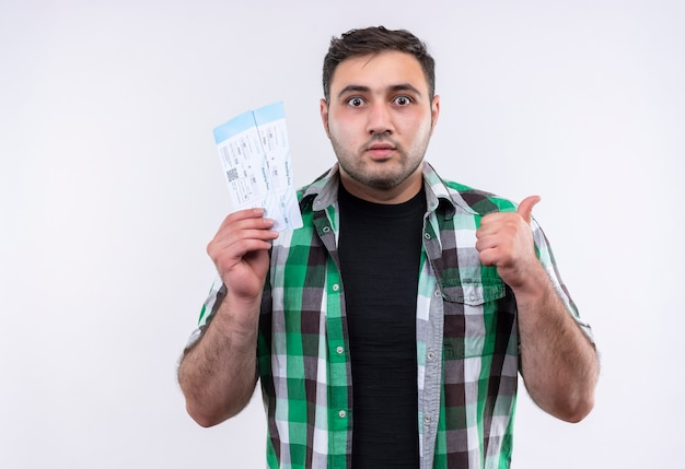 Young traveler man in checked shirt holding air tickets looking surprised showing thumbs up standing over white wall