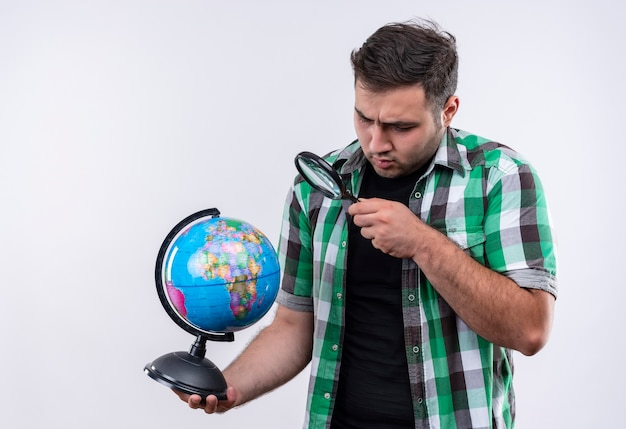 Young traveler man in checked shirt holding globe looking at it through magnifying glass looking surprised standing over white wall