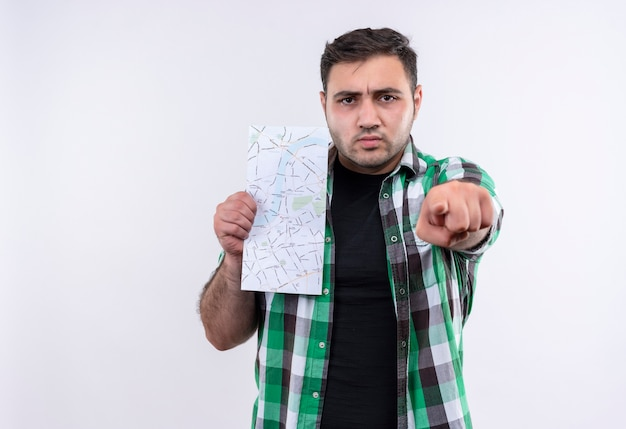 Young traveler man in checked shirt holding map pointing with finger to camera with frowning face standing over white wall