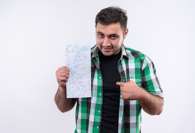 Young traveler man in checked shirt holding map pointing with finger to it looking confident standing over white wall