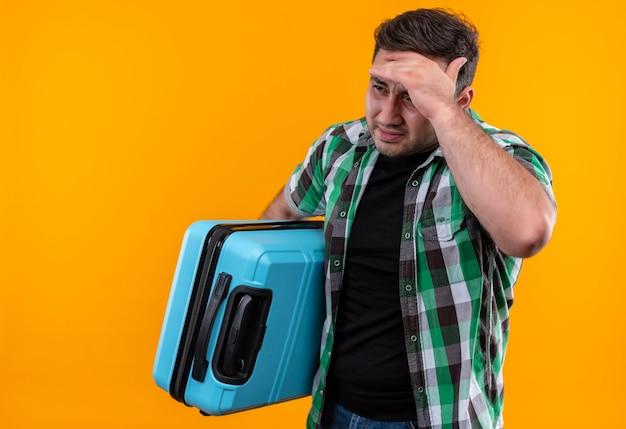 Uomo giovane viaggiatore in camicia a quadri tenendo la valigia guardando da parte confuso con la mano sulla sua testa per errore in piedi sopra la parete arancione