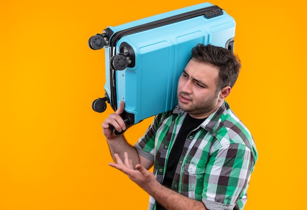 Young traveler man in checked shirt holding suitcase looking aside, displeased arguing standing over orange wall