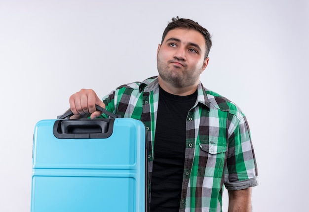 Young traveler man in checked shirt holding suitcase looking aside with sad expression on face standing over white wall