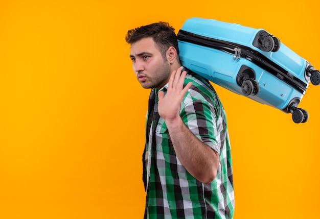 Uomo del giovane viaggiatore in camicia controllata che tiene la valigia che osserva da parte con la faccia seria che fluttua con la mano che sta sopra la parete arancione