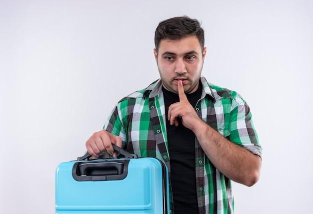 Uomo giovane viaggiatore in camicia controllata che tiene la valigia che fa gesto di silenzio con il dito sulle labbra in piedi sopra il muro bianco