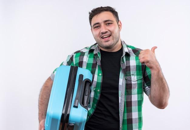 Uomo del giovane viaggiatore in camicia controllata che tiene la valigia che sorride allegramente che indica indietro che sta sopra il muro bianco
